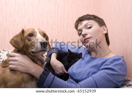 Young woman playing with her cat and dog on sofa in her apartment - stock photo