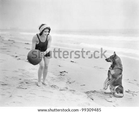 Young woman playing with her dog and ball on the beach - stock photo