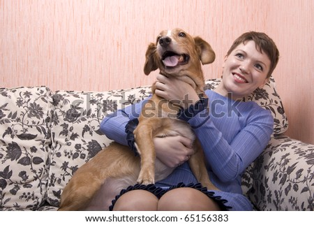 Young woman playing with her dog on sofa in her apartment - stock photo