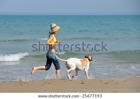 young woman playing with her dog on the beach