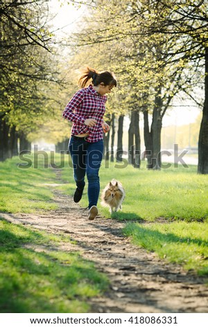 Young woman playing with her dog sheltie on the grass; training the shetland sheepdog in the park