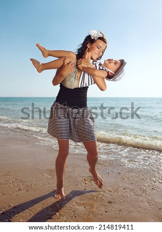 Young woman playing with her son at the sea coast. Summer vacation  - stock photo