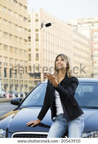 Young woman playing with keys of new car - stock photo