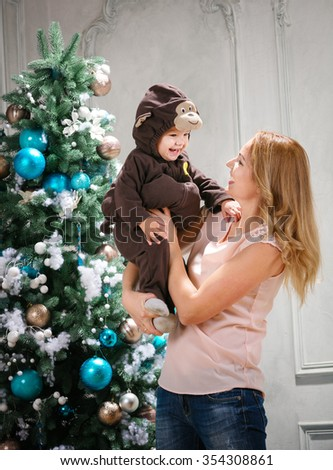 Young woman playing with little son dressed in monkey costume beside Christmas tree - stock photo