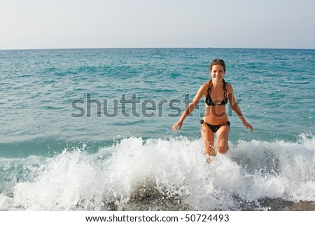 Young woman playing with waves on the beach
