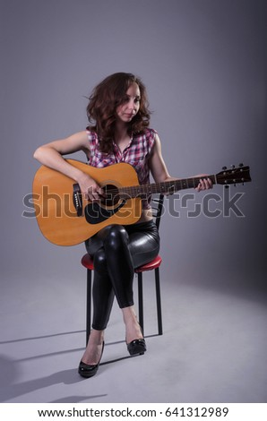 Young woman plays on an acoustic guitar, isolated on a gray background. A woman in leather pants and a shirt sits on a chair and holds a guitar.