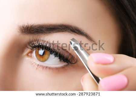 Young woman plucking eyebrows with tweezers close up - stock photo