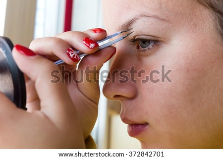 Young woman plucking eyebrows with tweezers close up. Cross processed image with shallow depth of field