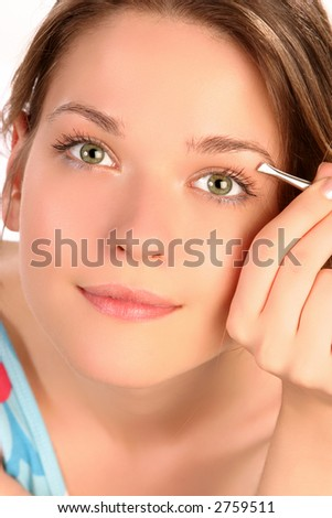 Young woman plucking her eyebrows with tweezers - stock photo