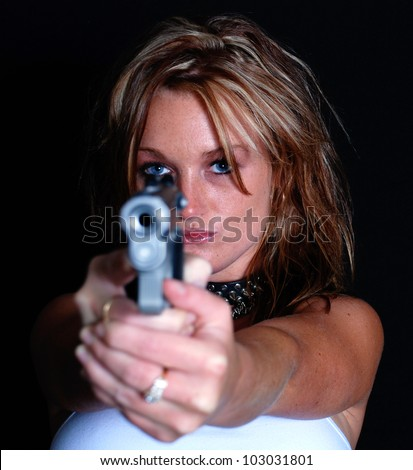 Young Woman Pointing a Gun with Main Focus on Woman - stock photo