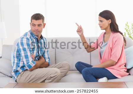 Young woman pointing at man while sitting on sofa at home - stock photo