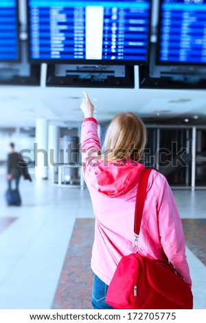 Young woman pointing on flight information in airport. - stock photo