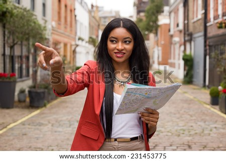 young woman pointing with a map - stock photo