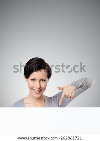 Young woman points down with forefinger , isolated on grey - stock photo