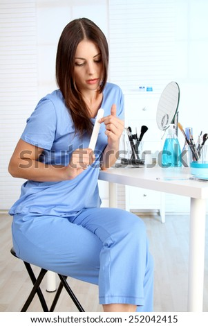 young woman polishes her nails - stock photo