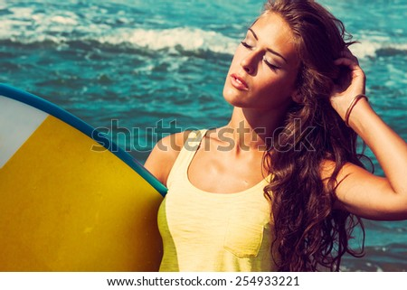 young woman portrait hold surfboard on seaside beach, sunny summer day - stock photo