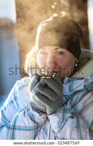 Young woman portrait holding mug wit hot tea outdoor at winter sunny day - stock photo