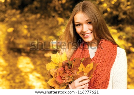 Young woman portrait in autumn park smiling at camera - stock photo