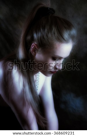 young woman portrait in dark studio shot profile