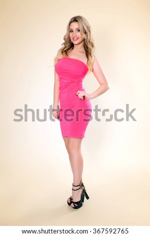Young woman portrait in pink. Beautiful smiling happy sexy full body portrait of pretty female fashion model in pink dress wearing high heels on yellow background - stock photo