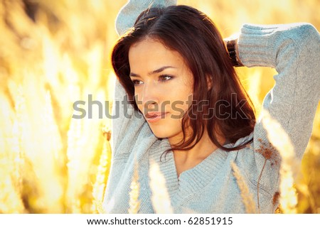 young woman portrait in yellow autumn field - stock photo