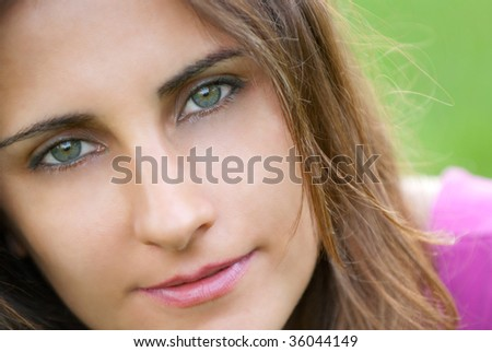 Young woman Portrait lying on nature grass - stock photo