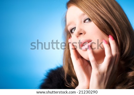 Young woman portrait. On blue background. Shallow dof. - stock photo