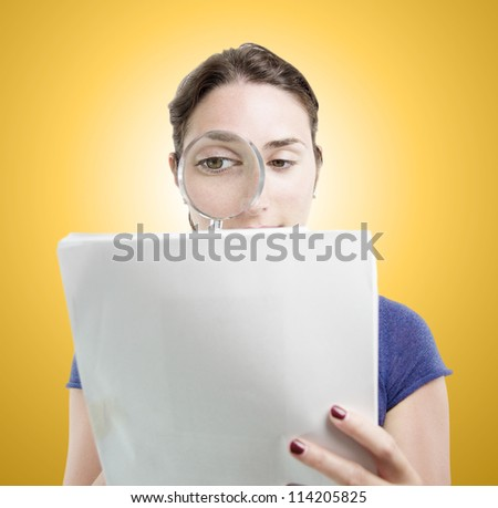 Young woman portrait over orange gradient background. She is researching documents with a magnifying glass - stock photo