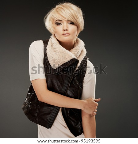 Young woman portrait. Shape and fit body beauty studio shoot. Healthy clean skin and perfect makeup on beautiful face of white model with short blonde hair. - stock photo