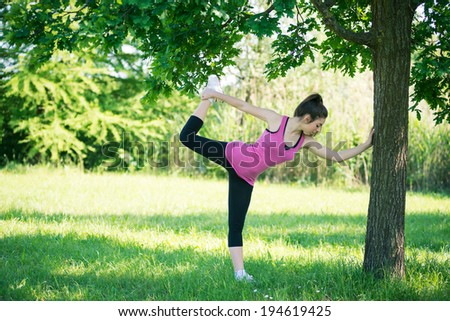 Young woman portrait stretching her legs outdoors in a park. - stock photo