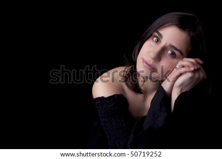 Young woman portrait with a pensive look on black background. - stock photo