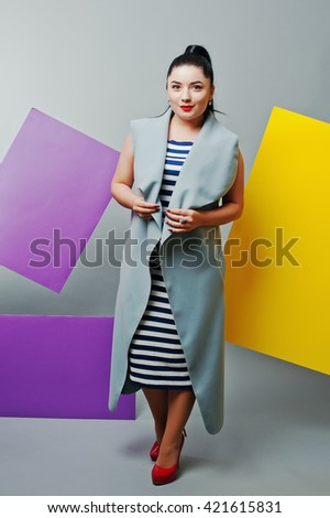 Young woman portrait with blank yellow and purple banner, board on gray isolated. - stock photo