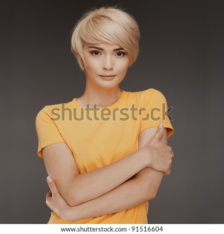 Young woman portrait with hair blond. Crossed arms. Confident look. - stock photo
