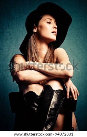 young woman portrait with hat, sit on chair, studio shot, small amount of grain added - stock photo