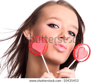 Young woman portrait with heart shaped lollipops. Isolated on white. - stock photo