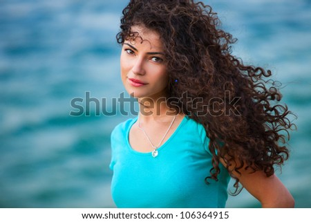 young woman portrait with long curly hair windy day by the sea summer time - stock photo