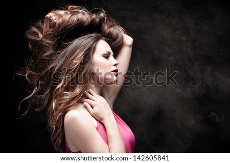 young woman portrait with long shiny healthy hair studio dark background - stock photo