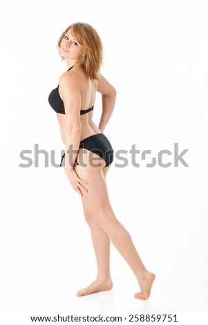 Young woman poses wearing a navy blue bikini  - stock photo