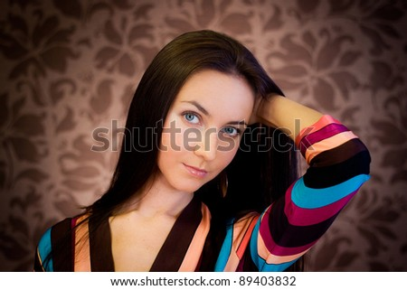 Young woman posing against brown retro wallpaper with floral design - stock photo
