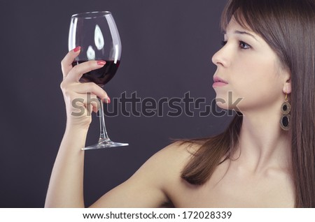 Young woman posing and looking at her glass of wine - stock photo