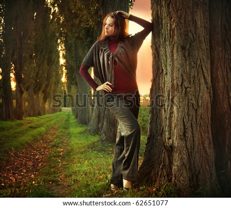 Young woman posing at autumn sunset - stock photo