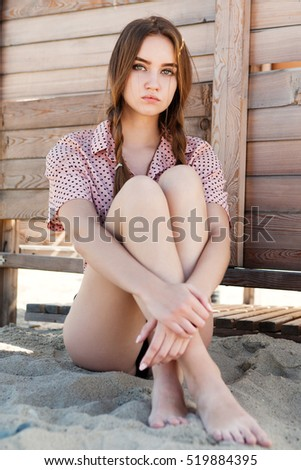 Young woman posing beside the wooden fence.
