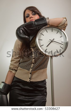 Young woman posing by the clock, wearing boxing gloves and looking self-confident - stock photo