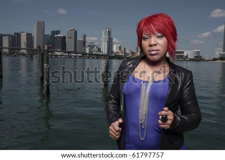 Young woman posing by the docks in a red wig - stock photo