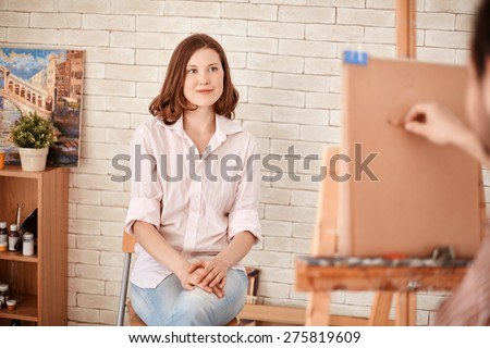 Young woman posing for artist in studio - stock photo
