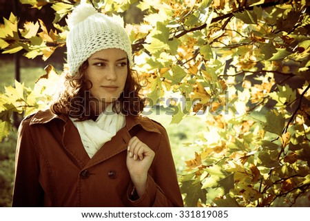 Young woman posing in a coat and with a cap in the front of yellow leaves - stock photo