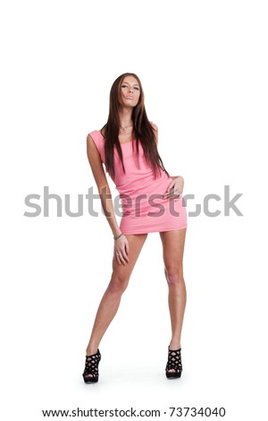 Young woman posing in a pink dress. Isolated over white background