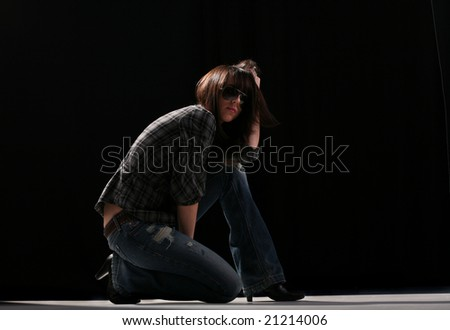 Young woman posing in dark with sunglasses - stock photo
