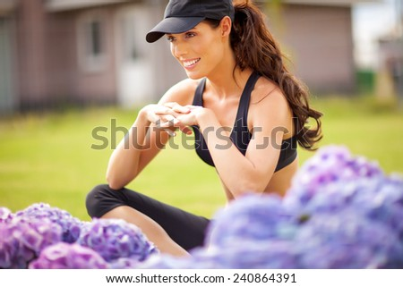 Young woman posing in fitness outfit in garden. Purple lush hydrangea and green grass downtown. - stock photo