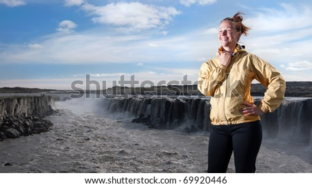 young woman posing in front of Selfoss waterfall, Iceland - stock photo
